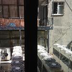 vue fenêtre ouverte de la chambre sur les moteurs de clim