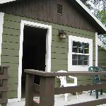 Front of cabin includes small deck with chairs, BBQ off to side