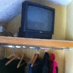 Old television on a shelf above a clothes rail...no waredrobe/s