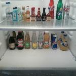 Mini bar in fridge with soda, liquor, water
