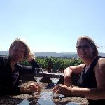 My best friend and I sitting on the deck of Goosecross with the vineyards behind us