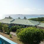 View from balcony, pool behind buildings, beach downhill, far far away...