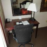 Room has a desk and rolling chair