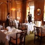 Waiters setting-up the oak panelled dining room
