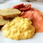 Delicious breakfast of cornbread, scrambled eggs, tomatoes and smoked salmon