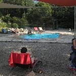 schöner Pool mit Sonnenschtutz und vielen Liegen