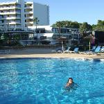 piscina con el hotel de fondo
