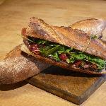 un sandwich MMM : roquette + tomates confites + jambon de pays + tapenade maison