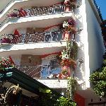 Flower decked balconies at the front of the hotel adds to the charm .