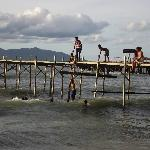 Local children jumping off pier.