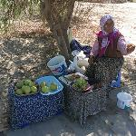 Lady selling fruit on the bath leading to the beach