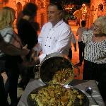 Le chef du restaurant servant une paella lors d'un repas familial