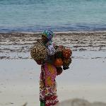 A lady on beach selling souvenirs