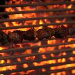 El Gaucho steaks cooked over a charcoal grill