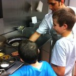 Boys making naan in the tandoor oven with the chef