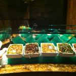 a triangular salad bar filled with hot and cold dishes