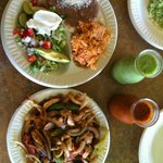 Chicken fajita, plate of beans, rice and toppings and flasks of salsa