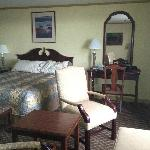 queen bed and desk and chair in oceanfront room