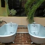 Two tubs on the open air second floor roof.