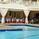 Außenansicht mit Essbereich am Pool zu Restaurant hin