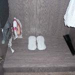 slippers, ironning board and an iron can be found in the cupboard