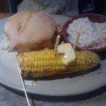 Some kind of chicken burger with coleslaw and corn on the cob