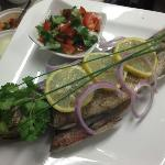 Grilled whole sea bass served with salsa