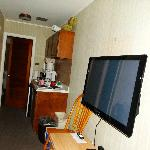 TV, kitchenette area and door to bedroom