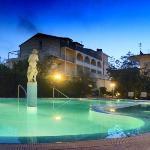 Nachtaufnahme vom Pool auf das Hotel