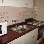 cosinha/com geladeira/microondas/pia/armários/copos/talheres/pratos