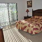 2nd bedroom with a queen bed, large closet and a tv. Has access to private screened porch.