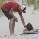 He showed her how to lie on the board before they went down to the water.