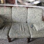 Old, mushy sofa with stained fabric.