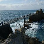 a un lado, vista de la pasarela y la Virgen de la Roca, al fondo