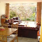 In a stylish open plan guest lounge are by-fold doors, opening out to a York Stone terrace for a