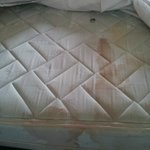 Terribly stained mattress with bottle caps under sheets!