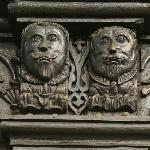 Detail of carved male figureheads on South screen