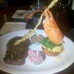 Grilled Ribeye, topped with lingonberry butter on lobster mac & cheese in a bread bowl