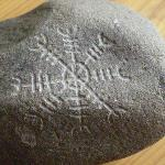 An etched rock with a good luck symbol