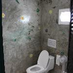 Wet room style bathroom, shiny concrete walls