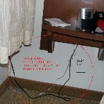 The messy wires for the lamp next to the bed and radio make room seem cheap.