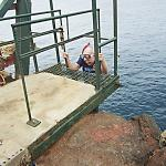 Older snorkel dude climbs up seawall/cliff access ladder
