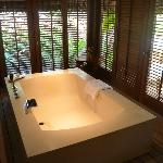 Huge bath tub in our villa with open doors to the garden