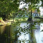 Het hotel vanuit de tuin met vijver en WW1 overblijfselen.