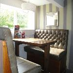 Interior pub decor with pedestal table & stone-brown vinyl booths