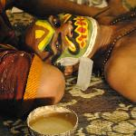 Kathakali performers preparing their make up