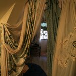 More boudoir curtains in doorway leading to bed area