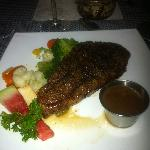 Delicious strip steak with peppercorn sauce and steamed vegetables