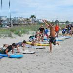 Teens learn to surf in the Ocean Lakes Billabong Surf camp (summer activities).