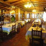 Interior del comedor, con un ambiente muy calido por la decorción en madera y la chimenea de le